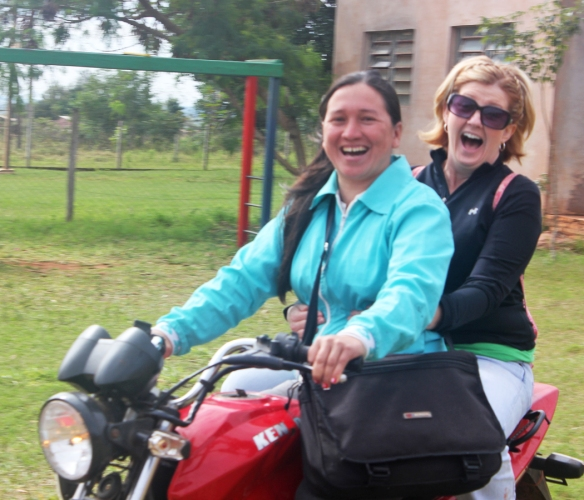 Mission team member in Paraguay riding on the back of a motorcycle.